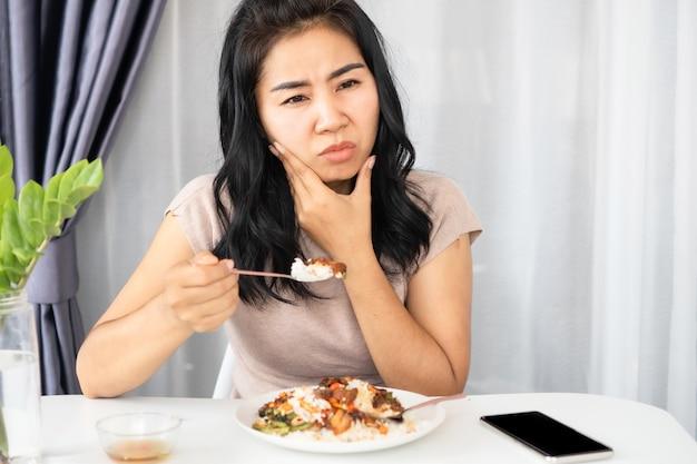 Mulher asiática tendo problemas com dente sensível à dor de dente ao comer