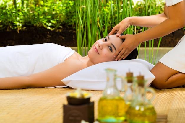 Mulher asiática, tendo uma massagem em ambiente tropical