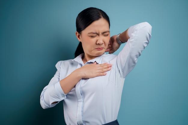 Mulher asiática testando cheirando a axila