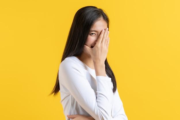 Mulher asiática tímida em um vestido casual cobrindo o rosto e espreitando