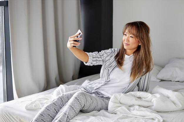 Mulher asiática tira foto na cama de manhã no fim de semana, jovem de pijama sentada aproveitando o tempo livre sozinha no quarto