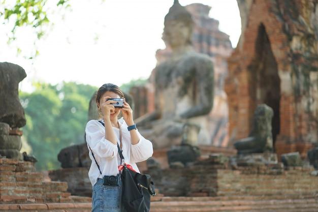 Mulher asiática tirando foto e viajando