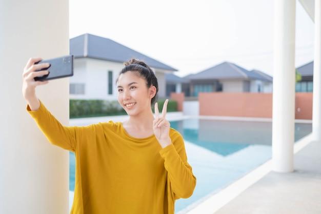 Mulher asiática tirando uma selfie com piscina