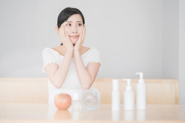 Mulher asiática tocando e verificando sua pele na sala