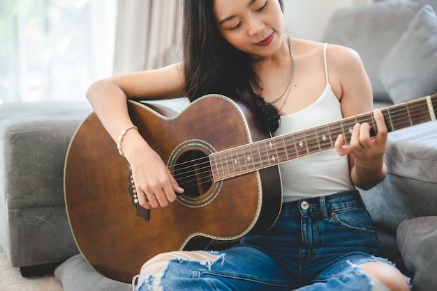 Mulher asiática tocando violão em casa, estilo de vida de jovem guitarrista músico com instrumento de arte acústica sentada para tocar e cantar uma música fazendo som em hobby na sala de casa