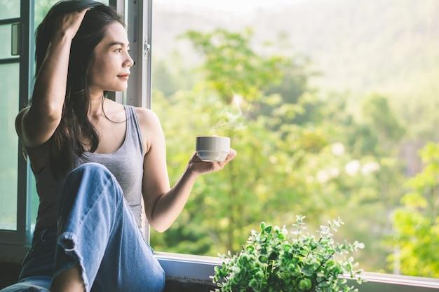 Mulher asiática tomando café ao lado da janela