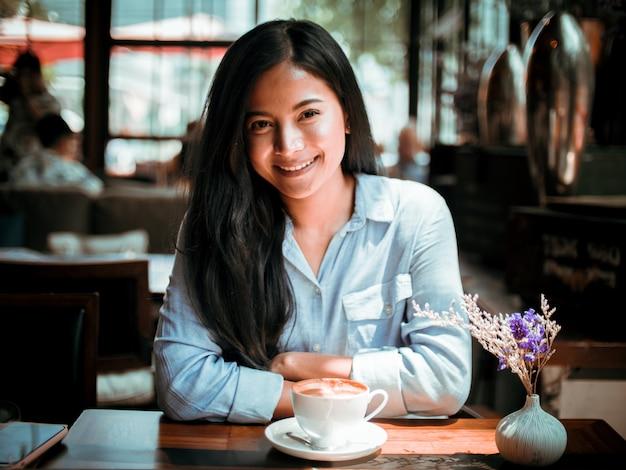 Mulher asiática tomando café e trabalhando com o computador portátil no café