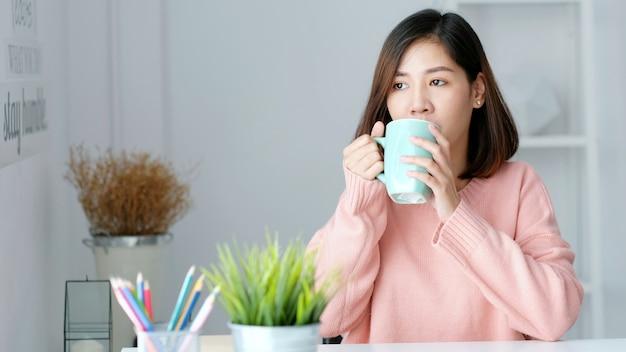 Mulher asiática tomando café enquanto está sentada no escritório em casa