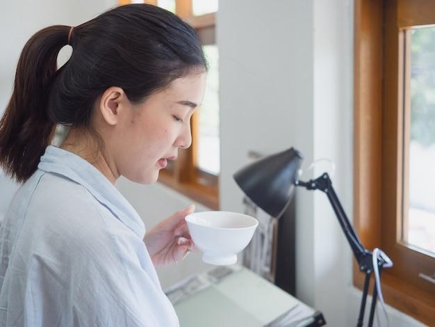 Mulher asiática tomando café na sala de trabalho