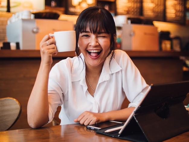 Mulher asiática tomando café no café e usando o computador portátil para trabalhar negócios