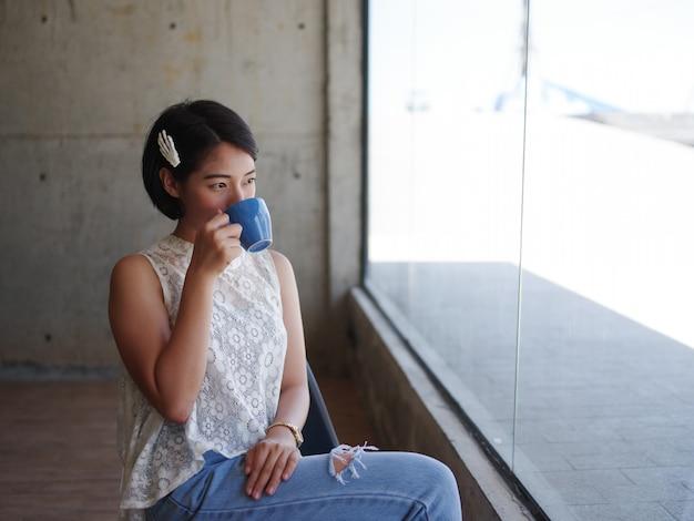 Mulher asiática tomando café no café