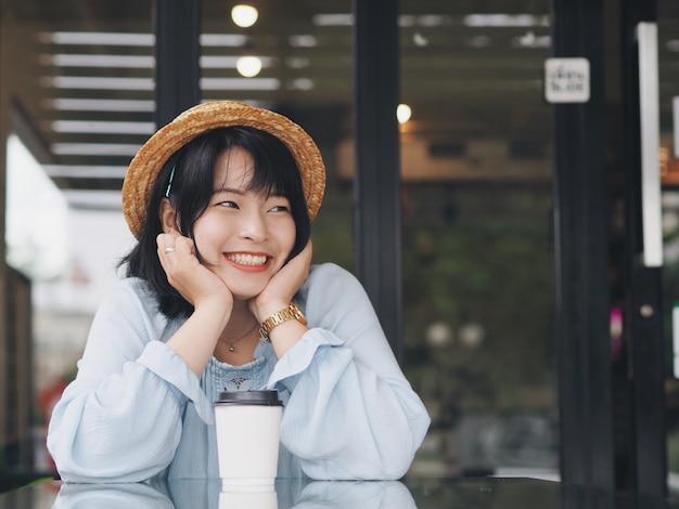 Mulher asiática tomando café no café.