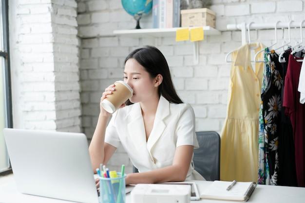 Mulher asiática tomando café no escritório