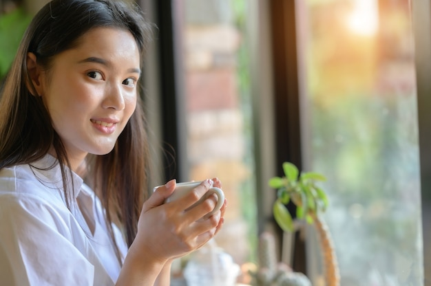 Mulher asiática tomando café