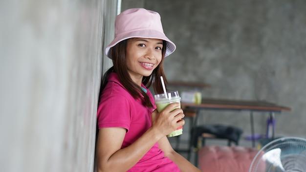 Mulher asiática tomando chá verde