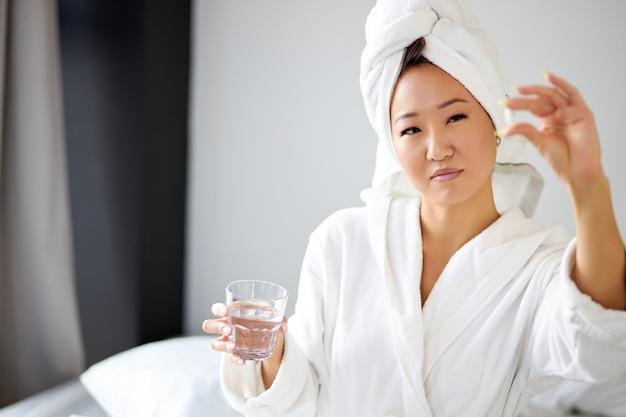 Mulher asiática tomando remédio depois de acordar pela manhã, mulher de roupão e toalha toma analgésico e sofre de enjôo matinal ou dor de cabeça