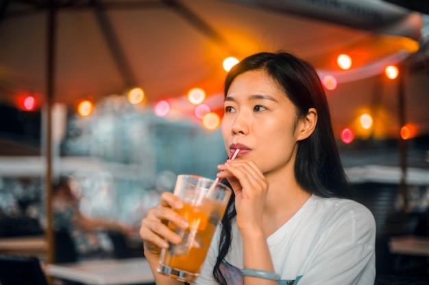 Mulher asiática tomando uma bebida no verão