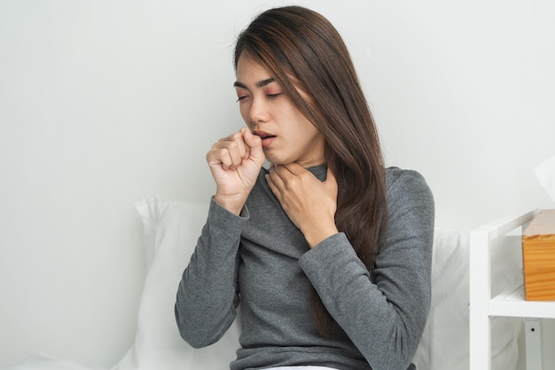 Mulher asiática tossindo na cama