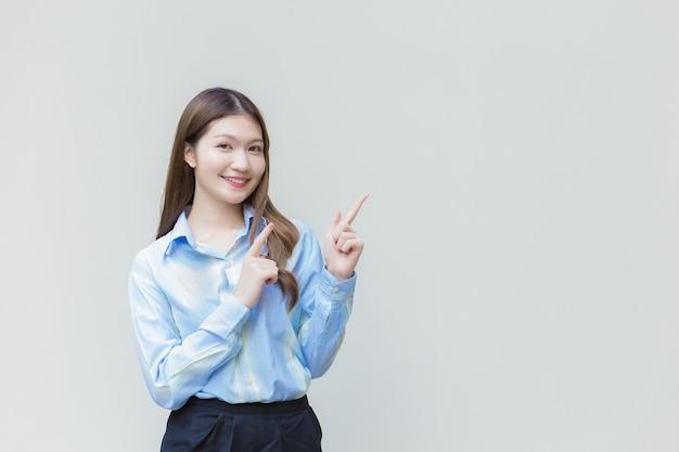 Mulher asiática trabalhadora com cabelo comprido, que usa uma camisa azul de manga comprida, sorri feliz