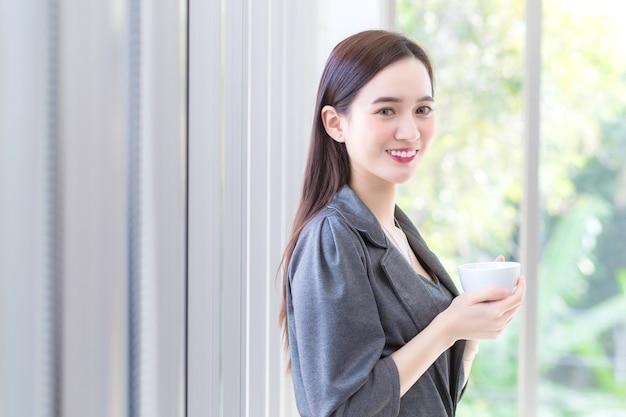 Mulher asiática trabalhadora com vestido cinza ergue-se e segura a xícara de café nas mãos pela manhã
