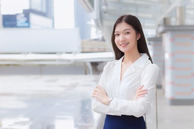 Mulher asiática trabalhadora confiante, com cabelo comprido e camisa branca, está em pé e cruza os braços em pé ao ar livre urbano enquanto caminha para o escritório em uma cidade grande com prédios comerciais com a cidade como