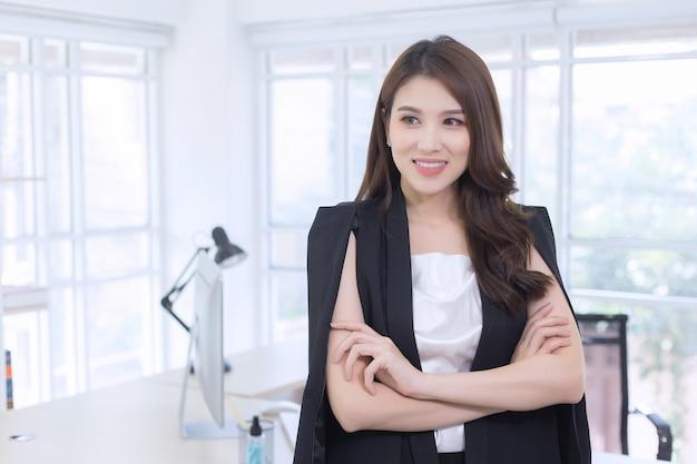Mulher asiática trabalhadora confiante, com cabelo comprido e um terno preto em pé e cruzando os braços
