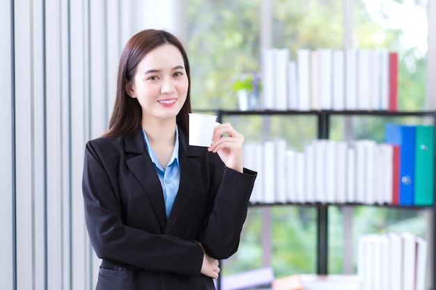 Mulher asiática trabalhadora em um terno preto segura um copo de papel para beber café pela manhã no escritório.