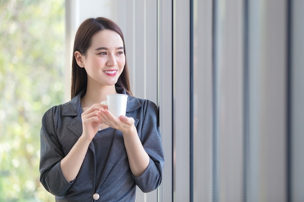 Mulher asiática trabalhadora olhando pela janela para pensar em algo enquanto segura uma xícara de café feita