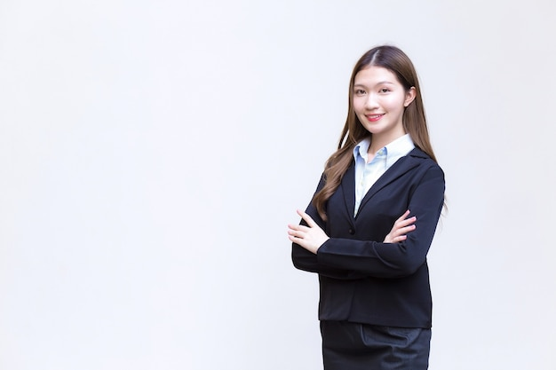 Mulher asiática trabalhadora que tem cabelo comprido usa um terno formal preto com camisa azul enquanto ela cruza o braço e sorri alegremente sobre fundo branco.