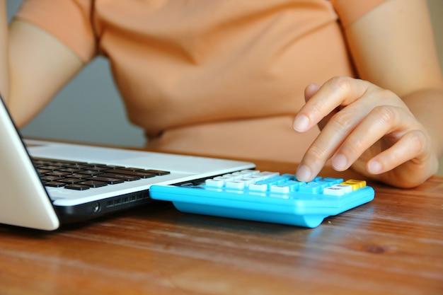 Mulher asiática trabalhando com laptop com a mão esquerda usando calculadora