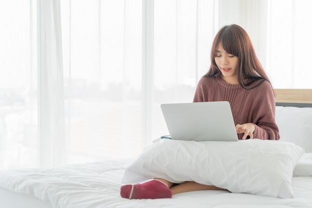 Mulher asiática trabalhando com laptop na cama