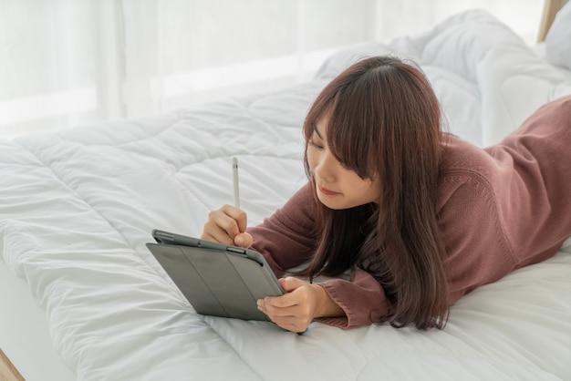 Mulher asiática trabalhando com tablet na cama