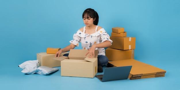 Mulher asiática trabalhando com uma caixa de produtos, conceito de venda de ideias on-line, loja de vendas on-line em casa