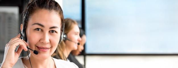 Mulher asiática, trabalhando em call center com equipe internacional