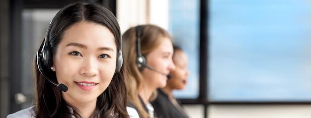 Mulher asiática trabalhando em call center com equipe internacional