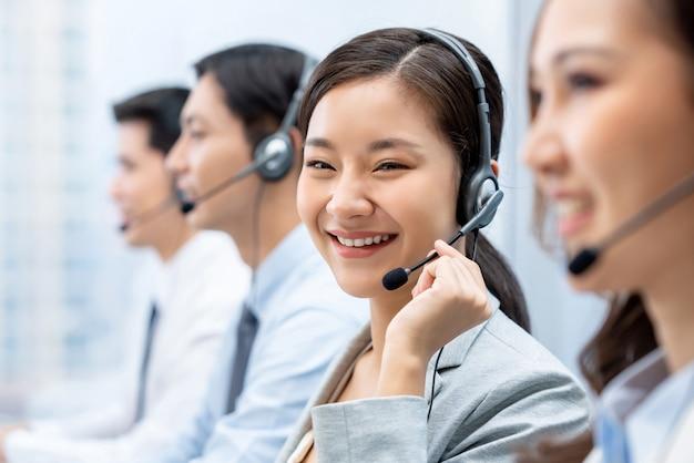 Mulher asiática, trabalhando em call center com equipe