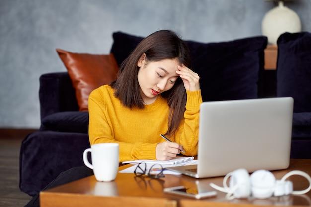Mulher asiática trabalhando em casa, escrevendo o caderno, freelancer. excesso de trabalho, preenchendo papéis