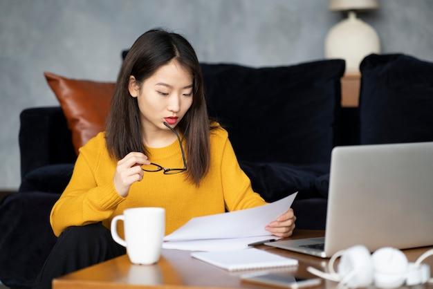 Mulher asiática, trabalhando em casa olhando documentos. linda freelancer japonesa