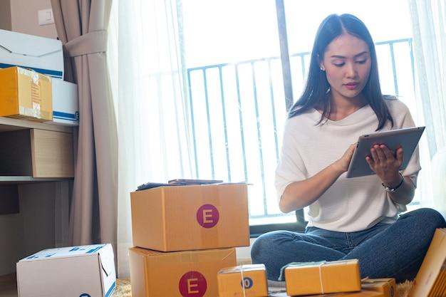 Mulher asiática trabalhando em casa para envio ao cliente