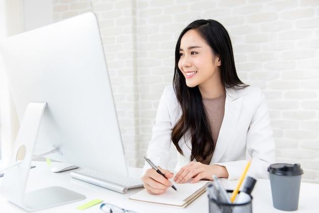 Mulher asiática, trabalhando em sua mesa no escritório