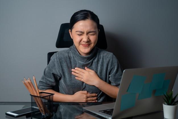 Mulher asiática trabalhando em um laptop estava doente, com dor de estômago, sentada no escritório