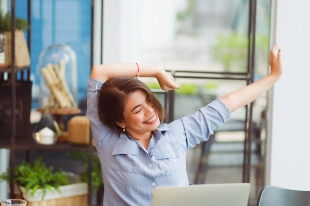 Mulher asiática, trabalhando no café e tem problema com síndrome do escritório