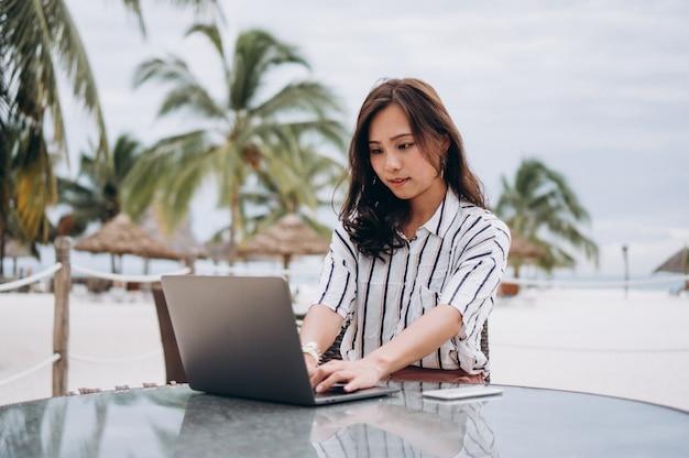Mulher asiática trabalhando no laptop em um período de férias
