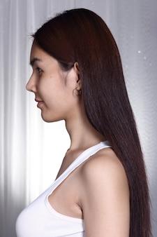 Mulher asiática transgênero antes de maquiagem estilo de cabelo. sem retoque, rosto fresco com pele bonita e macia. fundo cinza com iluminação de estúdio, vista traseira lateral