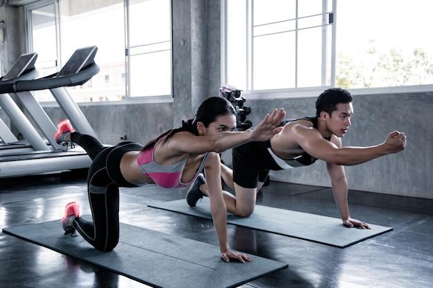 Mulher asiática treino parte inferior da coxa em um tapete de ioga com o homem treinador no ginásio. conceito de exercício no ginásio. mulher e homem treino no tapete de ioga.