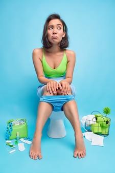 Mulher asiática triste e pensativa, sentada no vaso sanitário, parece descontente, lado a lado mantém as mãos nos joelhos