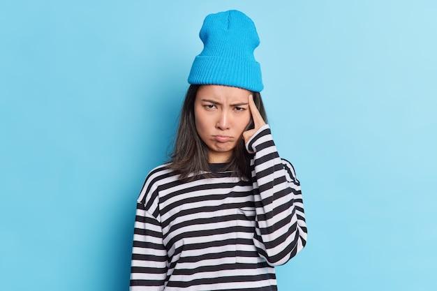 Mulher asiática triste e sombria com o dedo na têmpora olha tristemente para a câmera tentando se concentrar e tem expressão ofendida