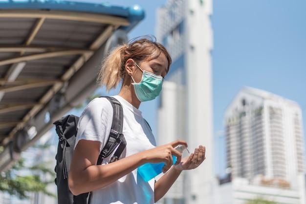 Mulher asiática usa gel de álcool desinfetante azul para as mãos para proteger o coronavírus, o fundo é um borrão do edifício na cidade, conceito covid-19