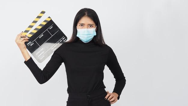 Mulher asiática usa máscara facial e claquete preto ou filme ardósia de exploração das mãos na produção de vídeo, cinema, indústria do cinema em fundo branco.