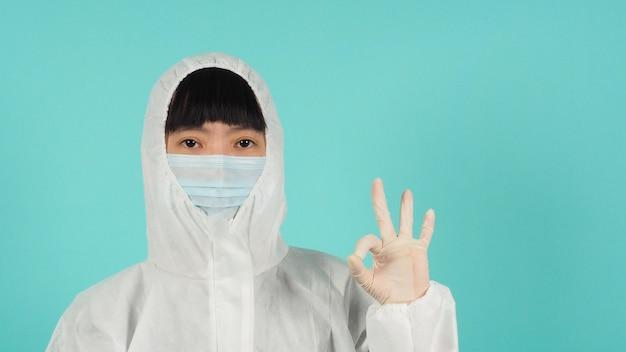 Mulher asiática usa máscara facial e terno ppe faz um sinal de mão ok no fundo verde menta ou azul tiffany.